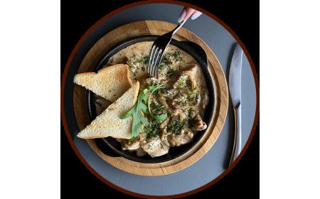 Куриные ломтики с грибами и сливками, поданные в сковороде